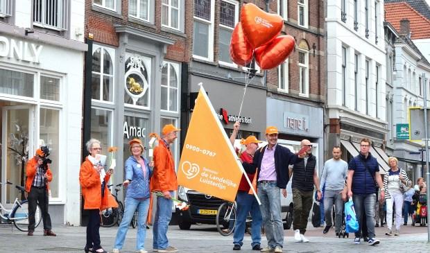 De vrijwilligers van Sensoor delen bloemen en flyers uit in de binnenstad van Den Bosch.