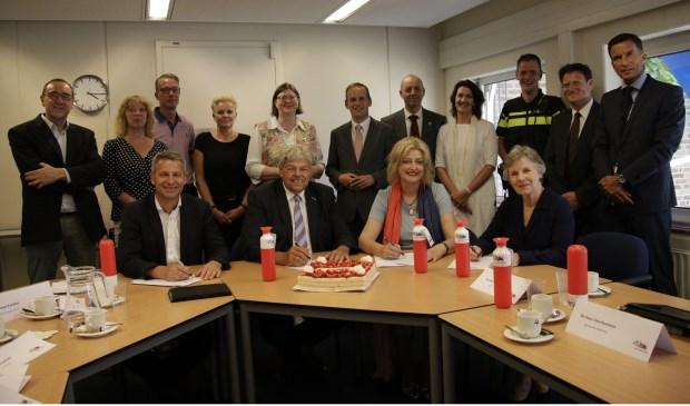 Burgemeester Melissant (met rode shawl) wordt omringd door diverse bestuurders en vertegenwoordigers van de samenwerkende partijen.Eigen foto