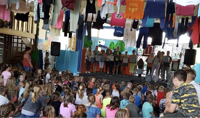 leerkrachten op het podium die in het zonnetje gezet worden door de leerlingen.