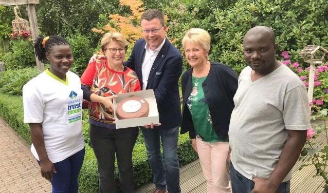Carla Brokking ontvangt de taart van de Rotaryvertegenwoordigers, terwijl haar gasten uit Oeganda toekijken. (Foto: Rotary)