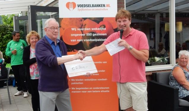 De heer G. van Buuren, voorzitter van de Voedselbank Nissewaard, kijkt nog een beetje beduusd als hij van Bernard Collens een cheque van 2800 euro uitgereikt krijgt en daar blijft het niet bij! Foto: Joop van der Hor