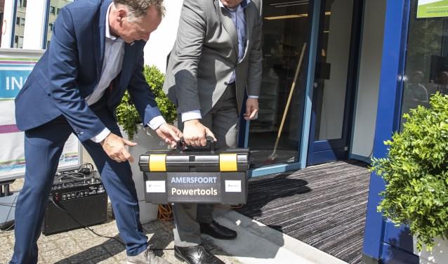 Directeur Dick van Maanen en wethouder Menno Tigelaar dragen een gereedschapskist het Geldloket in. Met de tools van Geldloket blijven inwoners financieel fit. (Foto: Patrick Siemons)