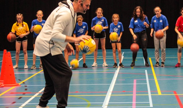 Oud-basketbalprof Henk Pieterse geeft een clinic tijdens 'Brug naar de Brugklas', een project waarbij toekomstige brugklassers uit de Maaspoort en Empel elkaar alvast leren kennen. Pieterse richt zich daarbij vooral op respect, de rode draad van de dag.