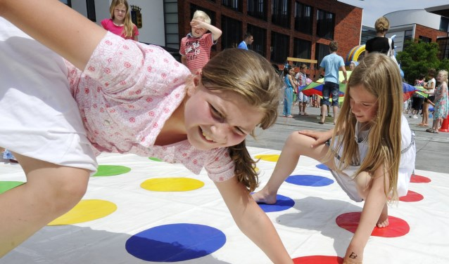 Kinderen spelen Twister in de buitenlucht tijdens buitenspeeldag. Foto: Carlo ter Ellen / Tubantia