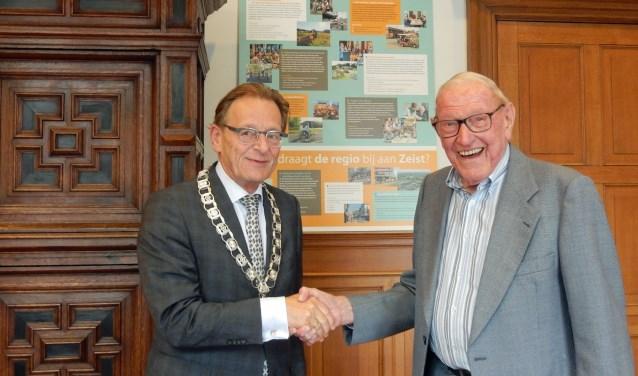 Koos De Kwaadesteniet (r) bij burgemeester Koos Janssen op zijn 100ste verjaardag. Dochter Jetje lokte haar vader met een smoes naar het gemeentehuis. De burgemeester zat in het complot.