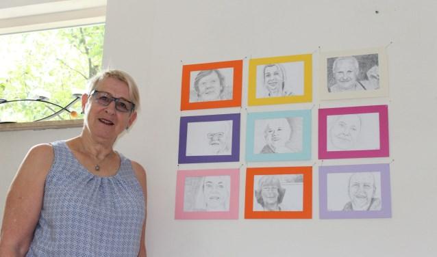 """Anneke Kruithof bij een deel van de portretten. """"Met het tekenen van zo'n zeventig straatgenoten, kwam mijn interesse in mensen en mijn passie voor tekenen samen."""" (foto: Sigrid Aalfs)"""