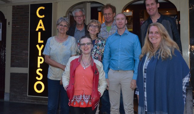 Na de voordrachtsavond poseerden de acht dichters voor Calypso. Vooraan in het rood Jolies Heij, de winnaar van de avond. - foto: Ben Blom