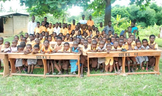 Lokaal gemaakte schoolbanken met de initialen van Stichting Ghana Schoolsupport. KG staat voor Kindergarten, alle meubels zijn genummerd.
