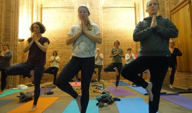 Deelnemers doen enthousiast mee aan yoga event in de Onze Lieve Vrouwetoren.