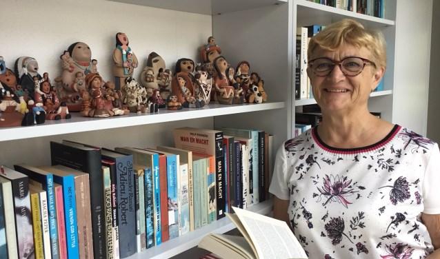 Hanny Jacobs voor de rijkelijk gevulde boekenkast met daarin haar verzameling 'storytellers'. (foto DFP)