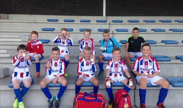 NEO25 Jongens onder de 9 jaar-team 2 is er supertrots op onder bezielende leiding van Lars de Bruijn (rechtsachter in het zwart) kampioen te zijn geworden. Maandag werd Lars door jongens en ouders in het zonnetje gezet.