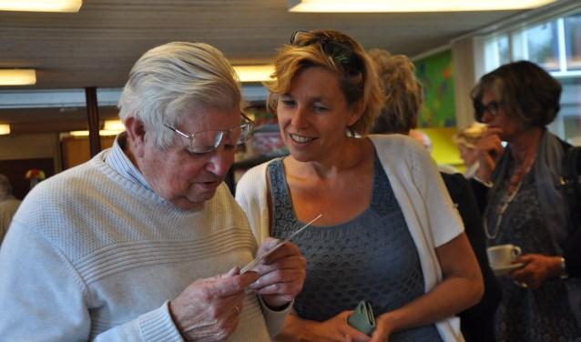Klaas Mandemaker, vroeger schoolhoofd en Debora de Bruijne, het huidige schoolhoofd, kijken naar oude schoolfoto's. FOTO: Anneke Flikweert
