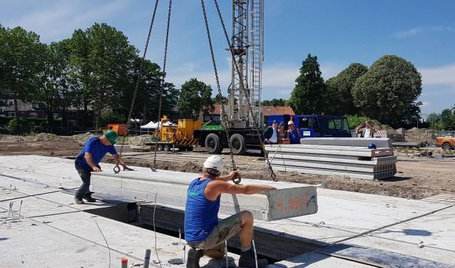 Liesbeth van Asten en Jan Jaap Kolkman leggen een begane-grondplaat op z'n plek. Daarmee is de bouw van de in totaal 83 woningen in De Venen, Rivierenwijk officieel gestart.