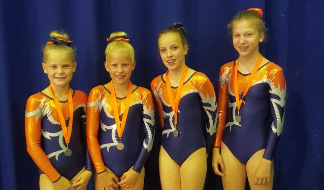 Linn te Veldhuis en Mady Brundel en Tara Buitenhuis en Renske Groen tonen vol trots hun medailles.