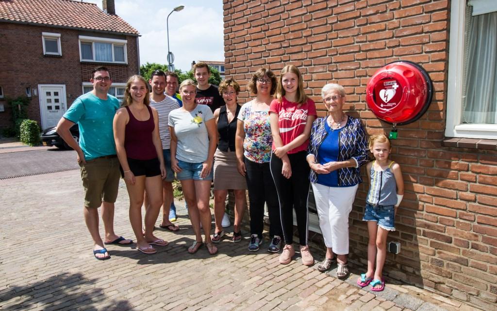 Monica van Hummel (vijfde van rechts) met familie en buurtbewoners bij de AED bij haar woning.