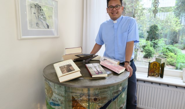 Pastoor Tuan Thanh Nguyen, hier bij het niet meer gebruikte doopvont uit de Sint-Henricuskerk in het Soesterkwartier, leest uiteenlopende genres boeken. Zijn favoriete boek was op het fotomoment uitgeleend (foto: Marian Vreugdenhil)