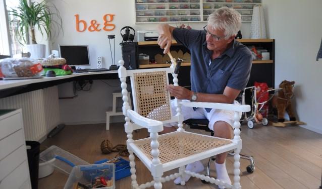 Bas de Vos met een door hemzelf van een nieuwe zitting voorziene stoel, met webbing. FOTO: Anneke Flikweert