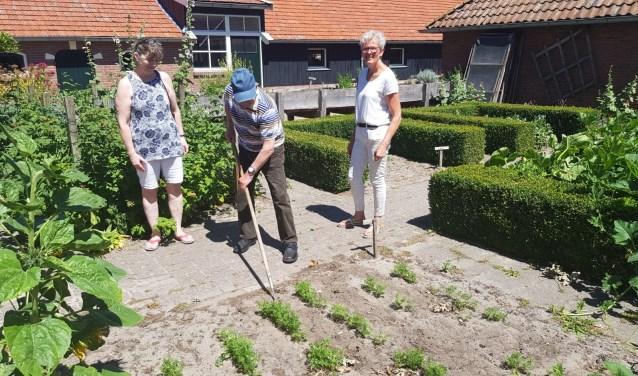 Marga Waanders (rechts) met enkele van haar cliënten. Waanders liet maandag enkele Canadezen zien hoe ze op Erve Knippert werken.