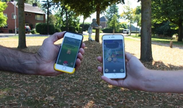 Digitaaltje (links) en zijn zoon tonen Pokémon-schermpjes op hun telefoons. FOTO: Jan Hermens