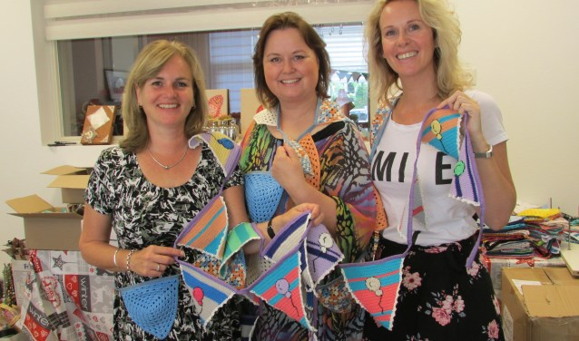 Nicole van der Woning, Debby Nijenhuis en Linda Smit met een klein stukje van de prachtige vlaggenlijn. Foto: Marjorie Nijbroek
