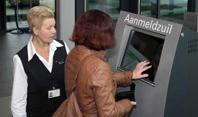 Een gastvrouw biedt assistentie bij een aanmeldzuil op locatie ETZ TweeSteden.
