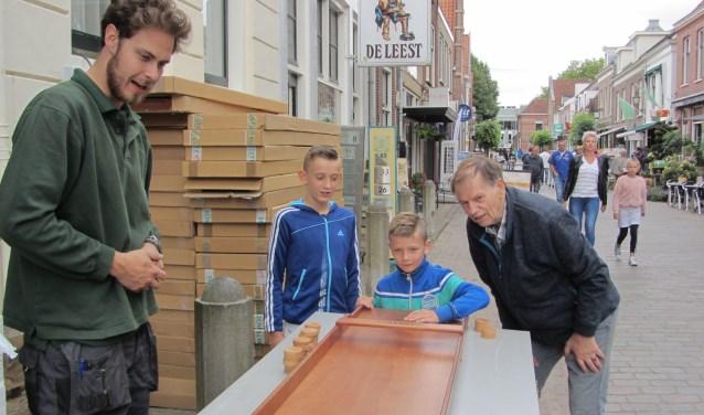 Schiltewerknemer Adrian (links) en voorzitter Adrie Rietveld van de Sjoelclub Nieuwegein e.o. kijken toe hoe jeugdige bezoekers proberen de meeste punten bij elkaar te sjoelen. (Foto: Lysette Verwegen)