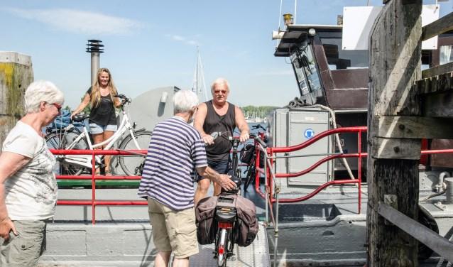 Op de Ms. Hoop (Wolphaartsdijk - Kortgene) helpen John en Tonny Beeke met veel plezier de fietsers die de oversteek wagen.