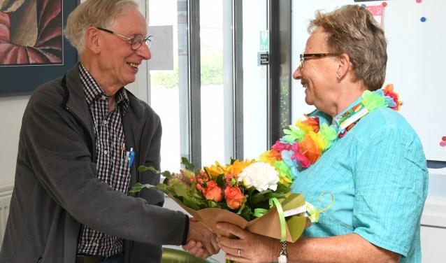 De vijfhonderdste deelnemer aan de Zomerschool 55+ krijgt tijdens de koffiepauze van de activiteit 'De kracht van ontrommelen' een bos bloemen overhandigd. Hij bezorgde de zomerschool een mijlpaal.