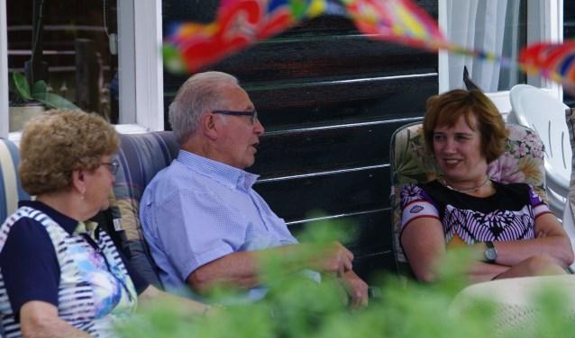 Echtpaar Stobbelaar-Wensink in gesprek met burgemeester Anneke Raven. Op de voorgrond wapperen vrolijk de vlaggetjes.