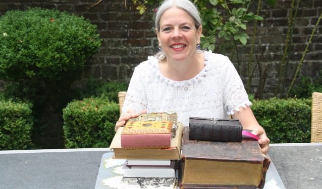Margareth met een deel van haar verzameling.'Ik ben altijd op zoek naar interessante bijbels.' FOTO: Astrid van Walsem