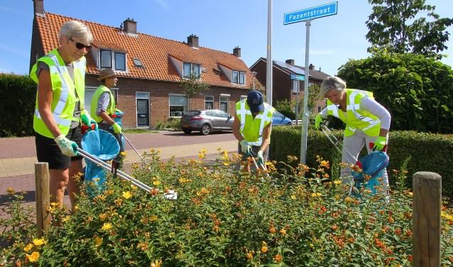 Vrijwilligers zijn in Driel op pad om op straat en in struiken zwerfvuil op te ruimen. (foto: Kirsten den Boef)
