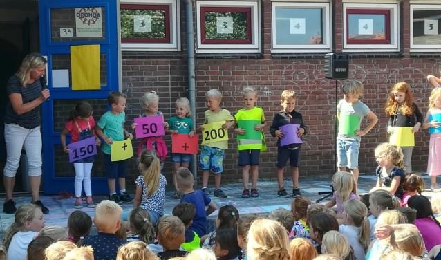 De kinderen tonen het bedrag dat ze voor Naomi bij elkaar hebben gelopen tijdens de sponsorloop.