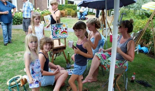 Als in de Tuin van Luijk schilder Wim van Geenen even geen zin meer heeft dan pakken de kinderen de kwast en maken het schilderij op hun manier af. Foto Dick Baas
