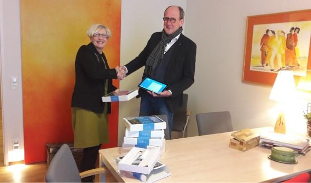 Anne aan de Wiel, lid van stichting Vrienden van Tiendwaert en Judith Leysterhof, overhandigt de tablets aan teamleider Piety Nijhoff. (Foto: Privé)