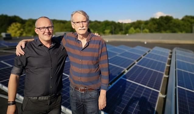 Aart de Goede (voorganger van Evangelische gemeente De Schuilplaats) en Wilco van der Kaaij (Alles op Groen) bij de zonnepanelen op het dak aan de Otterloseweg in Ede.