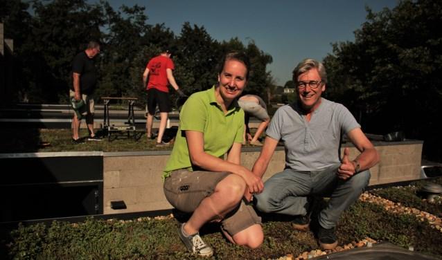 Inge Leijten en Henk Koops zitten op een van de nieuwe groene daken. Op de achtergrond zijn enkele buurtbewoners bezig met een ander dak. Het Kattenbosch project is het grootste in zijn soort in Nederland.