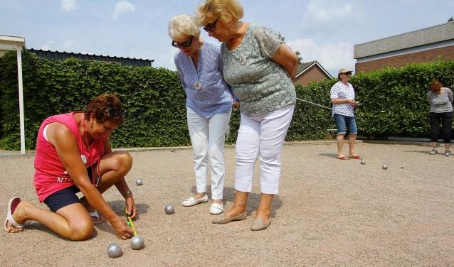 Annemarie van Deelen meet de afstand tussen de ballen. Dorien Reijmers (in het blauw) en Sjan Rousse kijken toe. (foto: Kirsten den Boef)