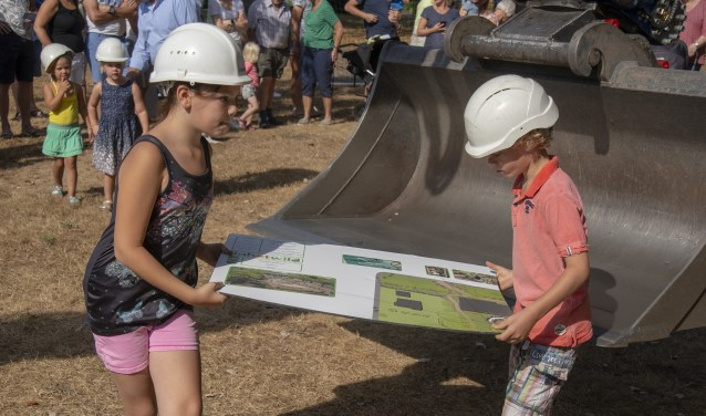 Kinderen halen puzzelstukken uit een  kraan en brengen ze via een kabelbaan bij vertegenwoordigers van gemeente, school en buurt.