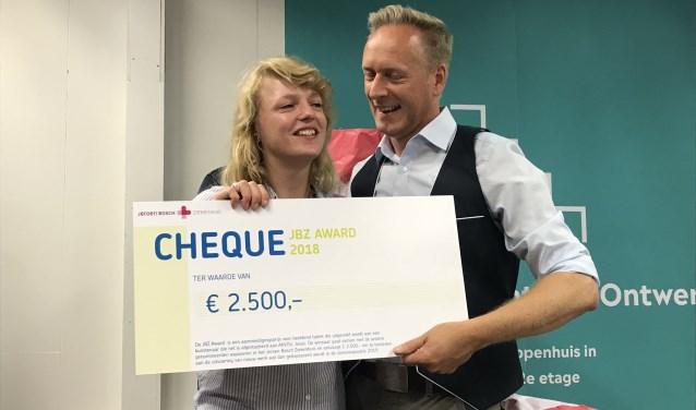 Jurylid Jean Marc Reinold overhandigt de cheque behorende bij de JBZ-Award aan de winnaar Lotte van der Pasch.