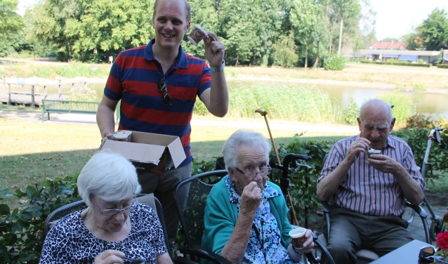 Burgemeester Joris Bengevoord deelt ijsjes uit aan de ouderen.