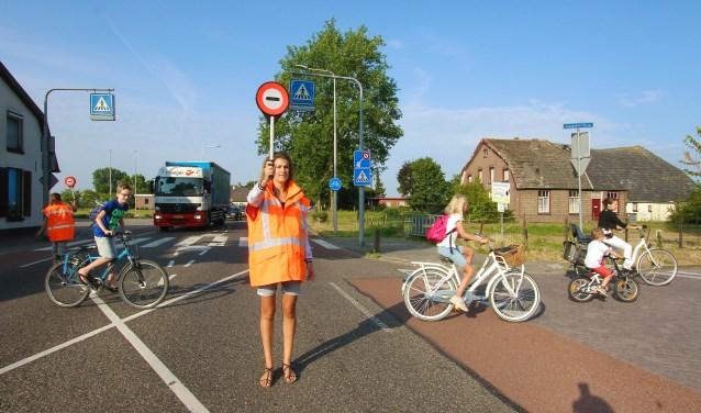 Dionne Derksen (voorgrond) en Ewelina Wagener helpen kinderen in alle vroegte bij het oversteken op de Karstraat. (foto: Kirsten den Boef)