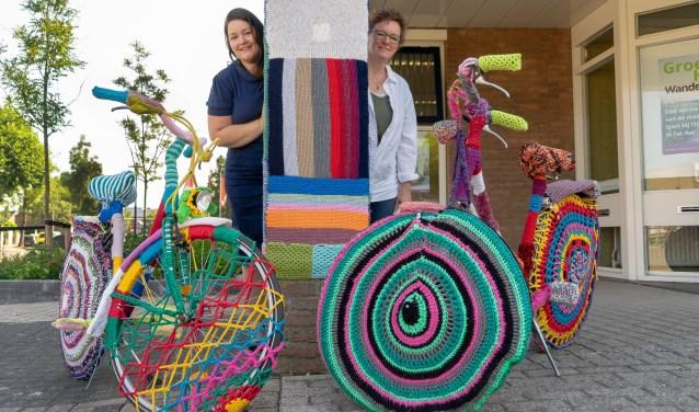 Op de foto achter de fietsen en pilaar: links Eveline en rechts Barbara Zornig.