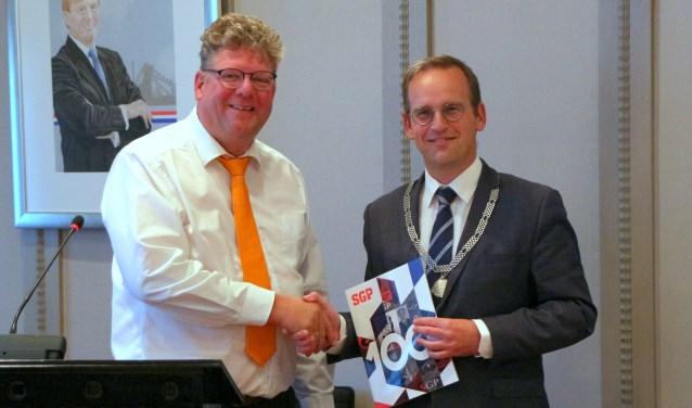 Peter Hoogendoorn, voorzitter van SGP-Sliedrecht overhandigt de jubileumglossy van de SGP aan burgemeester Bram van Hemmen.