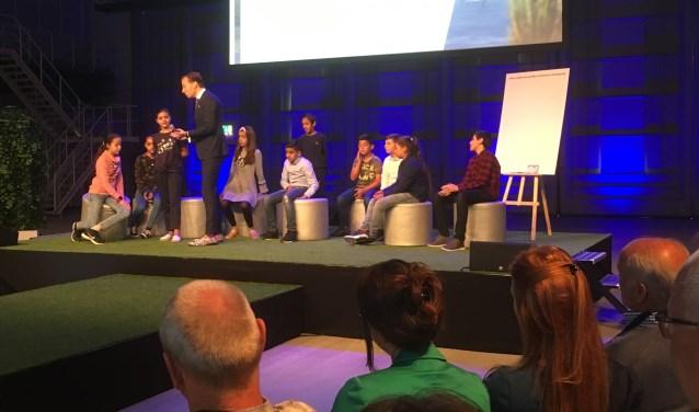 Leerlingen van een basisschool uit Den Haag beantwoorden vragen op een bijeenkomst over de toekomst van de natuur in Zuid-Holland.