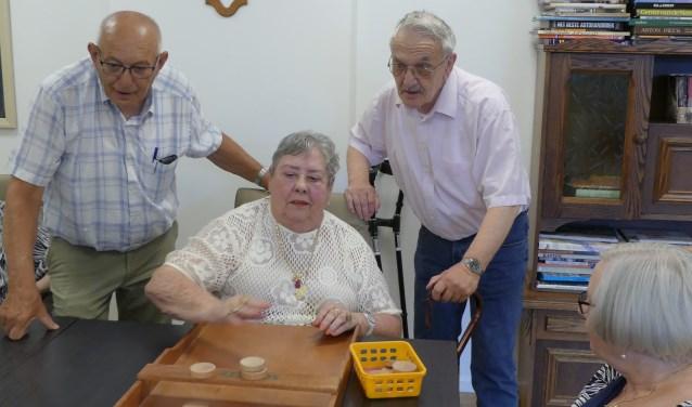 V.l.n.r. vrijwilliger 'sjoelen en tuin' Gerrit Besselsen, cliënten mevrouw Ciska Wijnen en de heer Henk van Hernen.