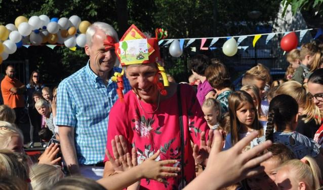Juf Wilma Dijkstra wordt hartelijk ontvangen op het plein door de kinderen van Het Baken