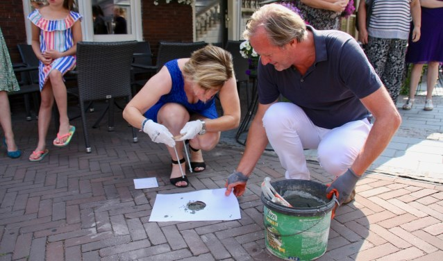Wethouder Marieke Frank steekt met hulp van Peter Konings voorlopig de laatste munt in het wegdek van de Markt.