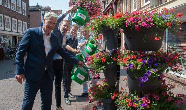 Wethouder Hans Buijtelaar, Jan Bouwman, Maikel Gijzen en Erwin Lubberding geven de bloemen water. (Foto: Ronald Kersten Fotografie)