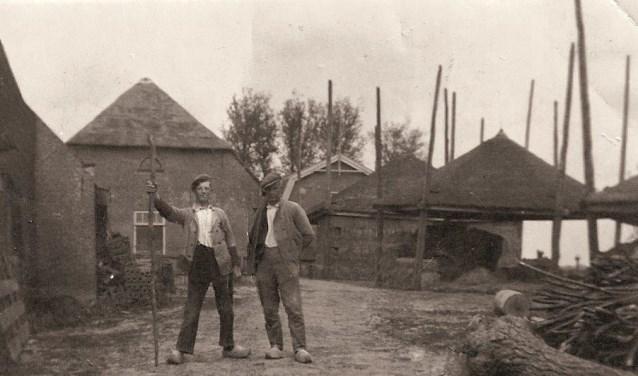 Boerenknecht Bregman (links) werkzaam op de boerderij.
