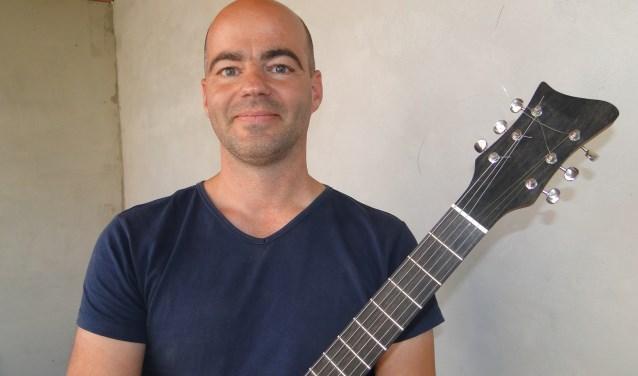 Léon Van de Heg met de gitaar die hij maakt voor Gitaarwerk.